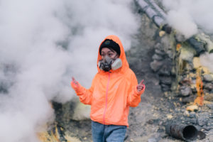 Brightly-colored Volcano Tourist with gas maskin Sulfur Mine