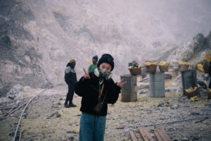 Tourist with gas mask poses for photo with sulfur miners in the background